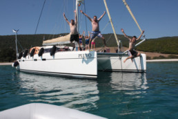 Happy charter clients jumping from pluto catamaran