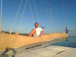 A happy charter client on the boom of Pluto catamaran